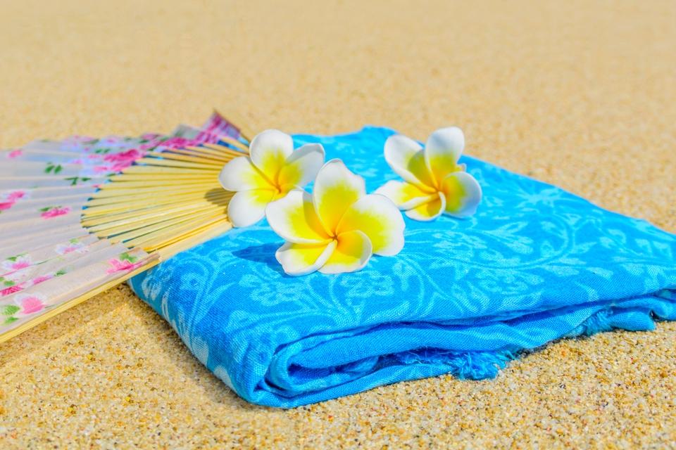 A beach towel, fan and flower accessory.
