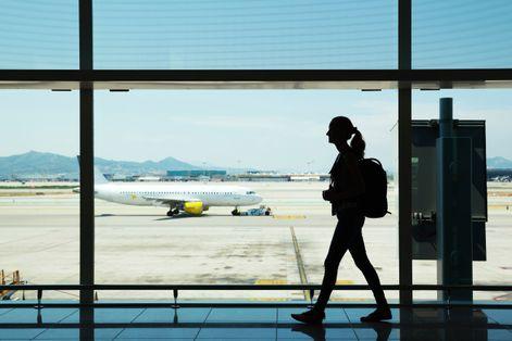 Γυναίκα περπατάει σε διάδρομο αεροδρομίου
