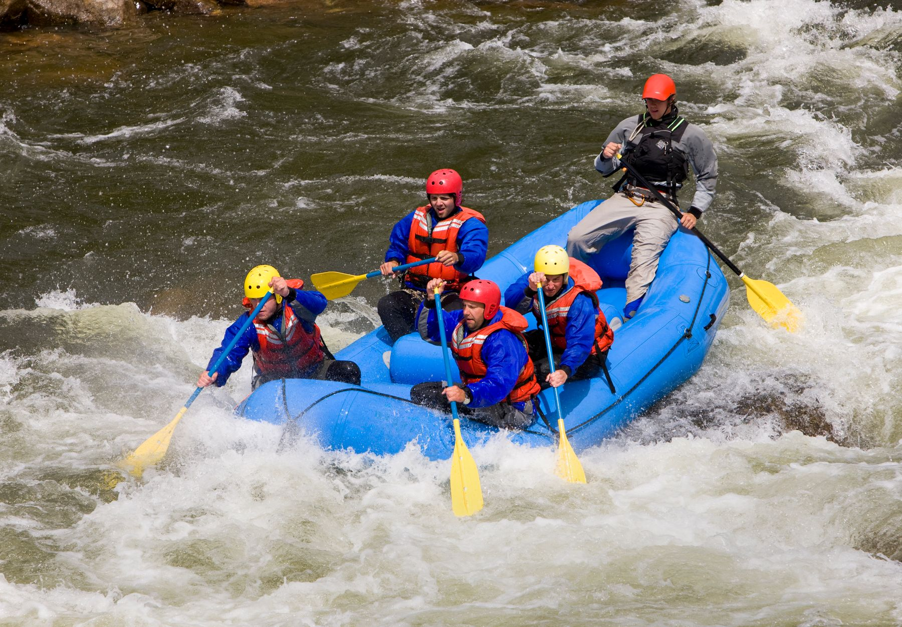 People whitewater rafting along the river.
