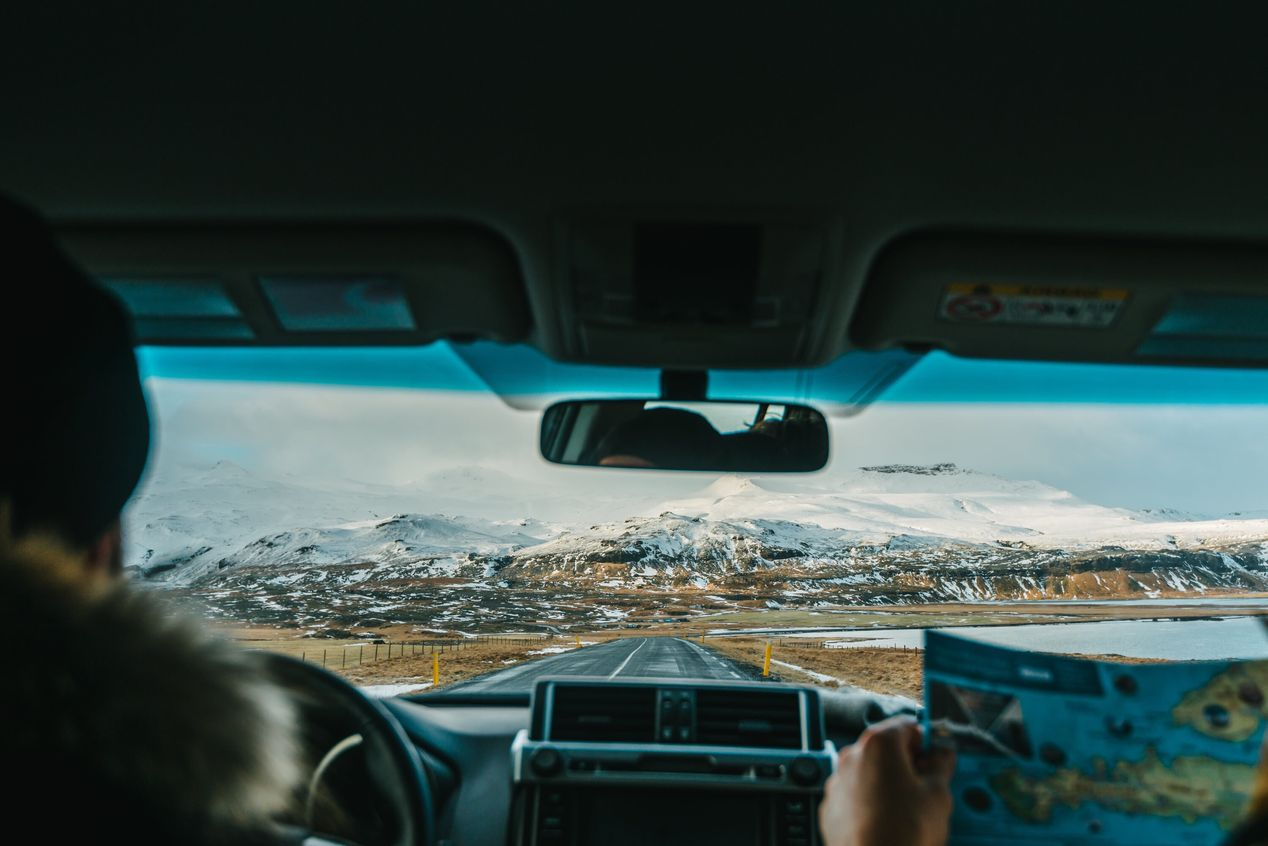 Couple driving towards snow-capped mountains - travel insurance, is it worth it?