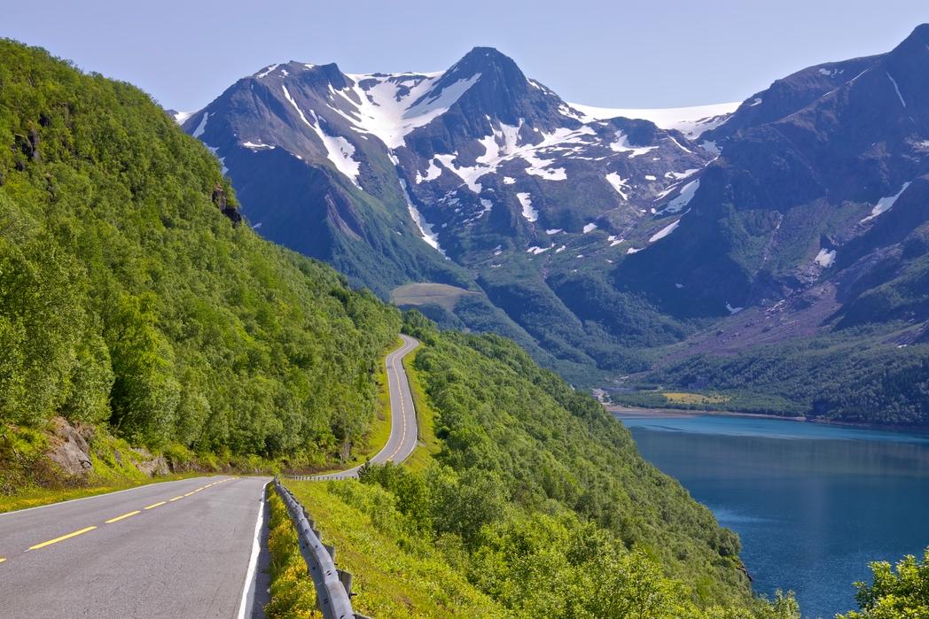Οδική διαδρομή δίπλα σε λίμνη και χιονισμένες βουνοκορφές