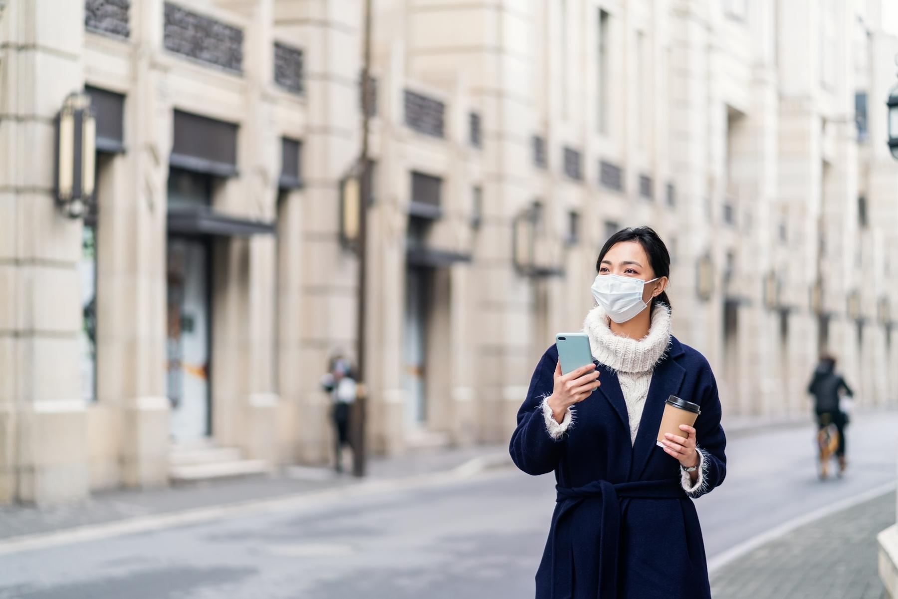 Девушка в маске держит в руке смартфон