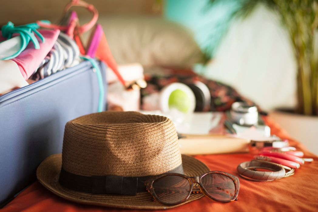 Wondering what you can take on a plane? A sunhat and sunglasses as well as various other items like a camera and jewellery next to a packed suitcase on a table.