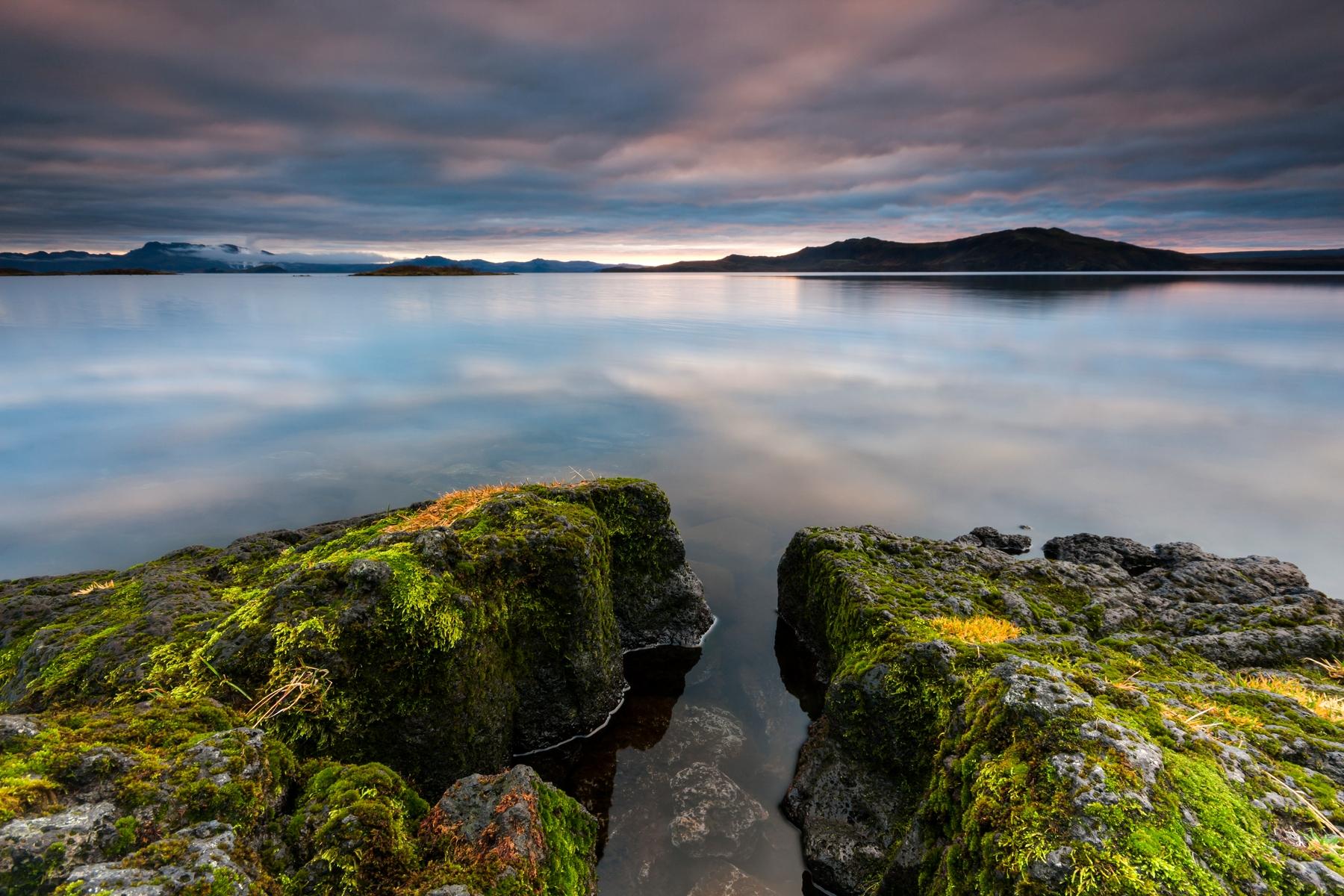 L'eau vitreuse et les roches couvertes de mousse sous un ciel maussade