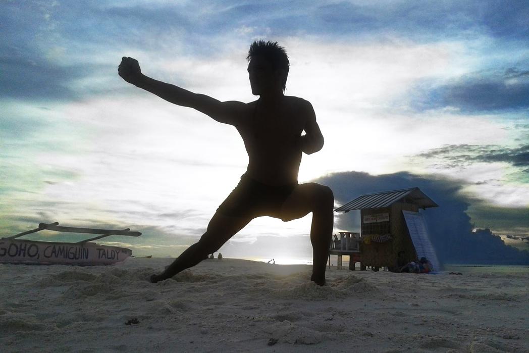 Άνδρας κάνει γιόγκα στην παραλία
