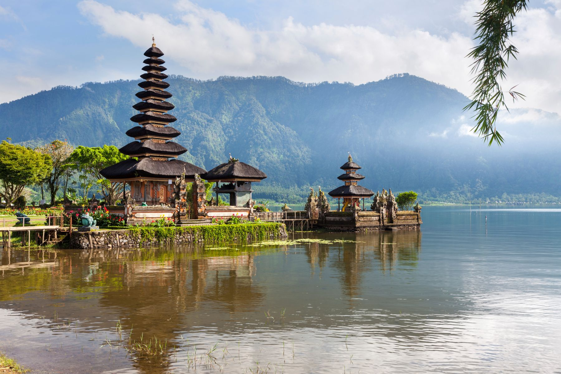A temple in Bali, jutting out into a placid lake with with atmospheric misty mountains in the background