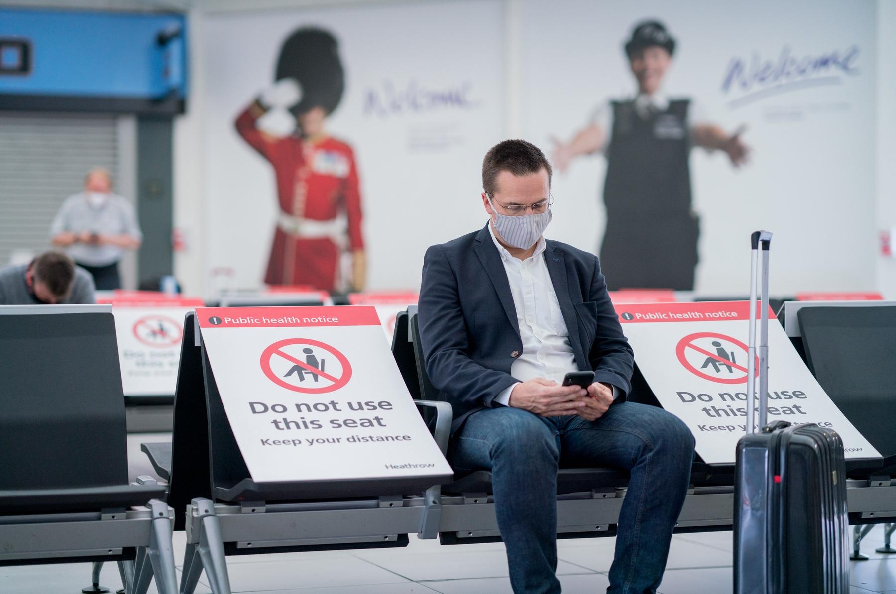 Man waiting at airport during coronavirus