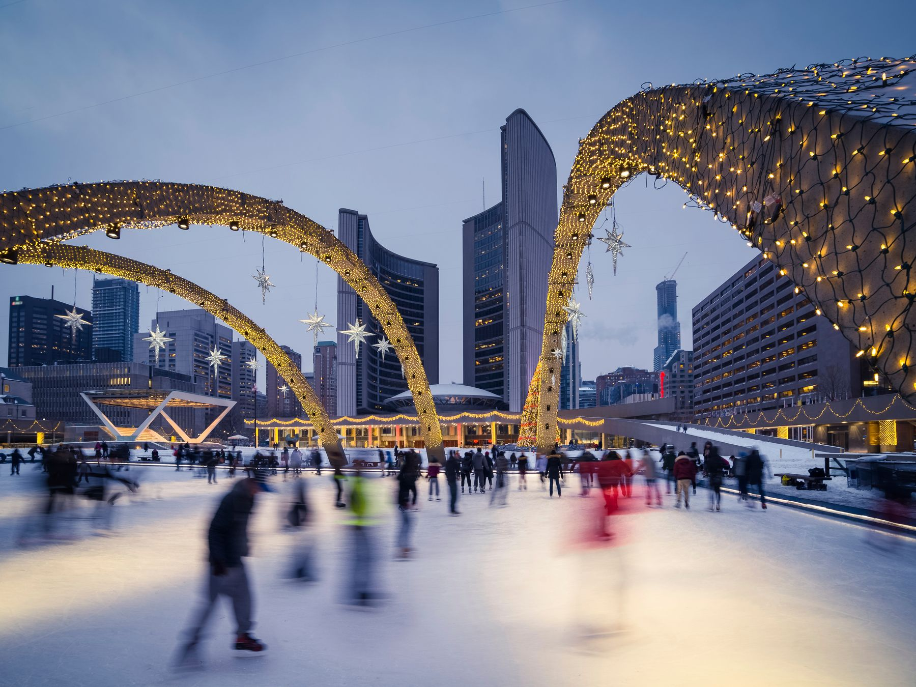 fast-motion shot of people skating at Nathan Phillips Square in Toronto, a popular winter activity and thing to do in Toronto