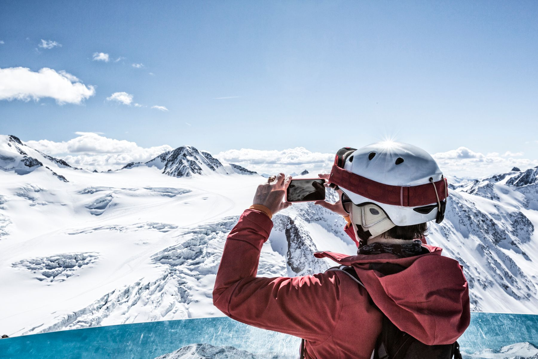 Skiier standing at top of mountain taking a photo of the scenery on their smartphone