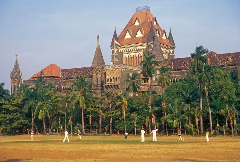 Άντρες παίζουν κρίκετ μπροστά από ένα ιστορικό κτίριο περιτριγυρισμένο από φοίνικες, Μουμπάι, Ινδία