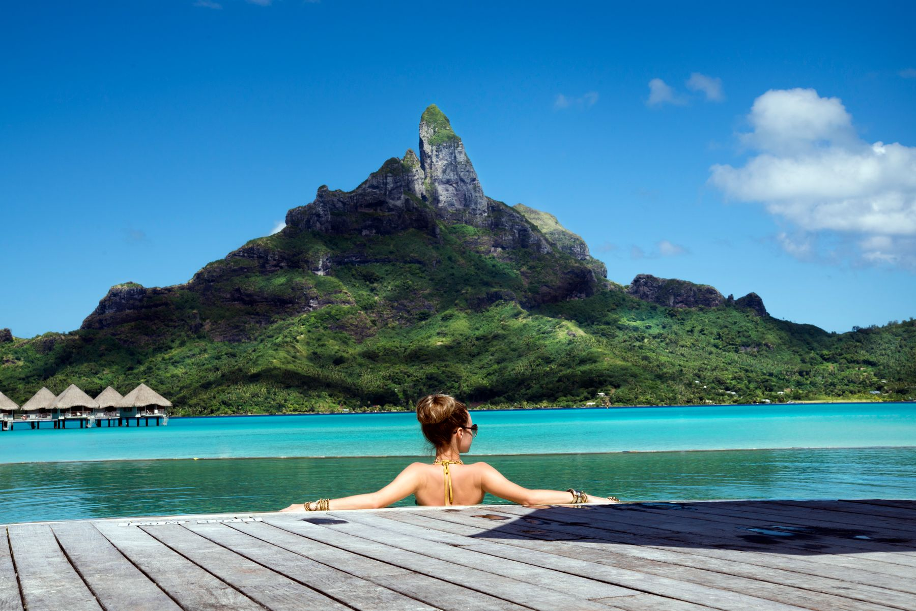 person resting  by the pool in Tahiti with the view of a mountain. Tahiti is the ultimate dream vacation destination