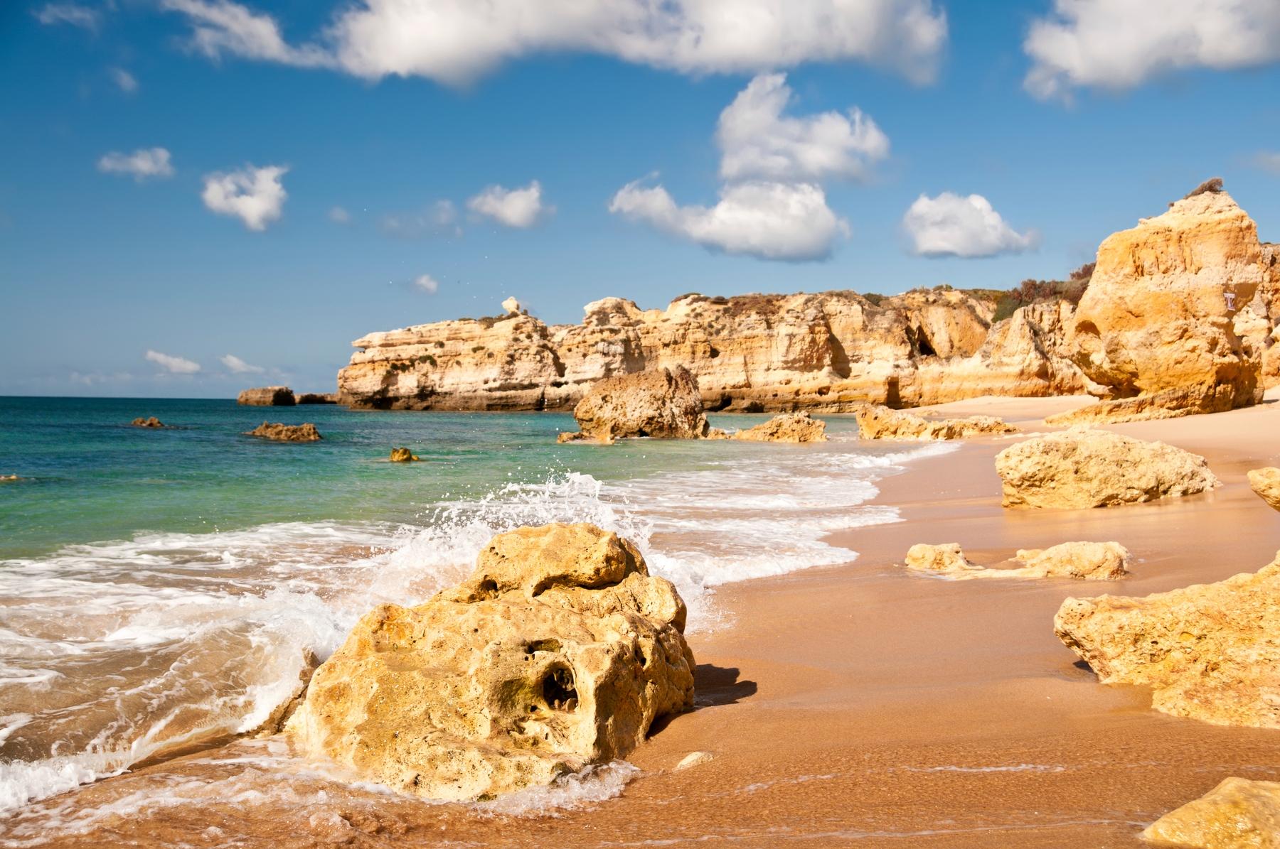 Sandy, empty beach linesd by sea cliffs in the Algarve Portugal.