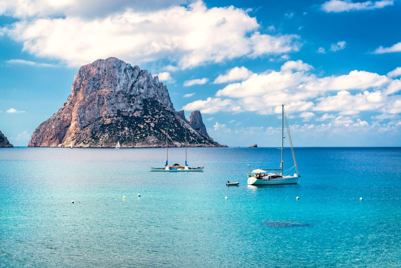 Boats around the uninhabited islan of Es Vedra in Ibiza, Spain