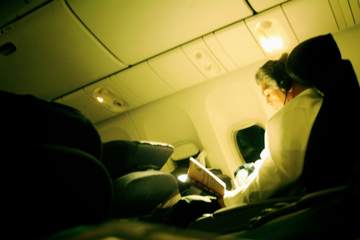 Man in the airplane cabin reading with headphones on