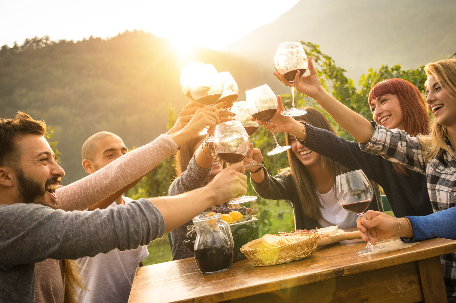 Group of friends celebrating and toasting their glasses of wine at a sunset dinner