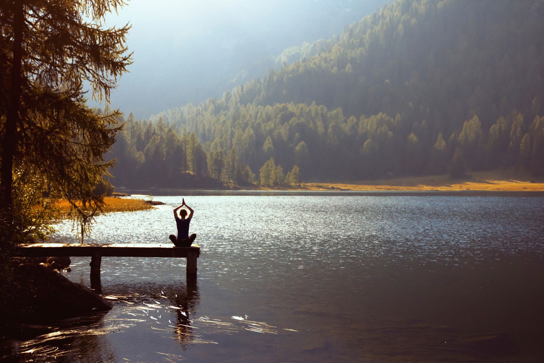 a lake and mountain view with a person doing a yoga pose from a distance