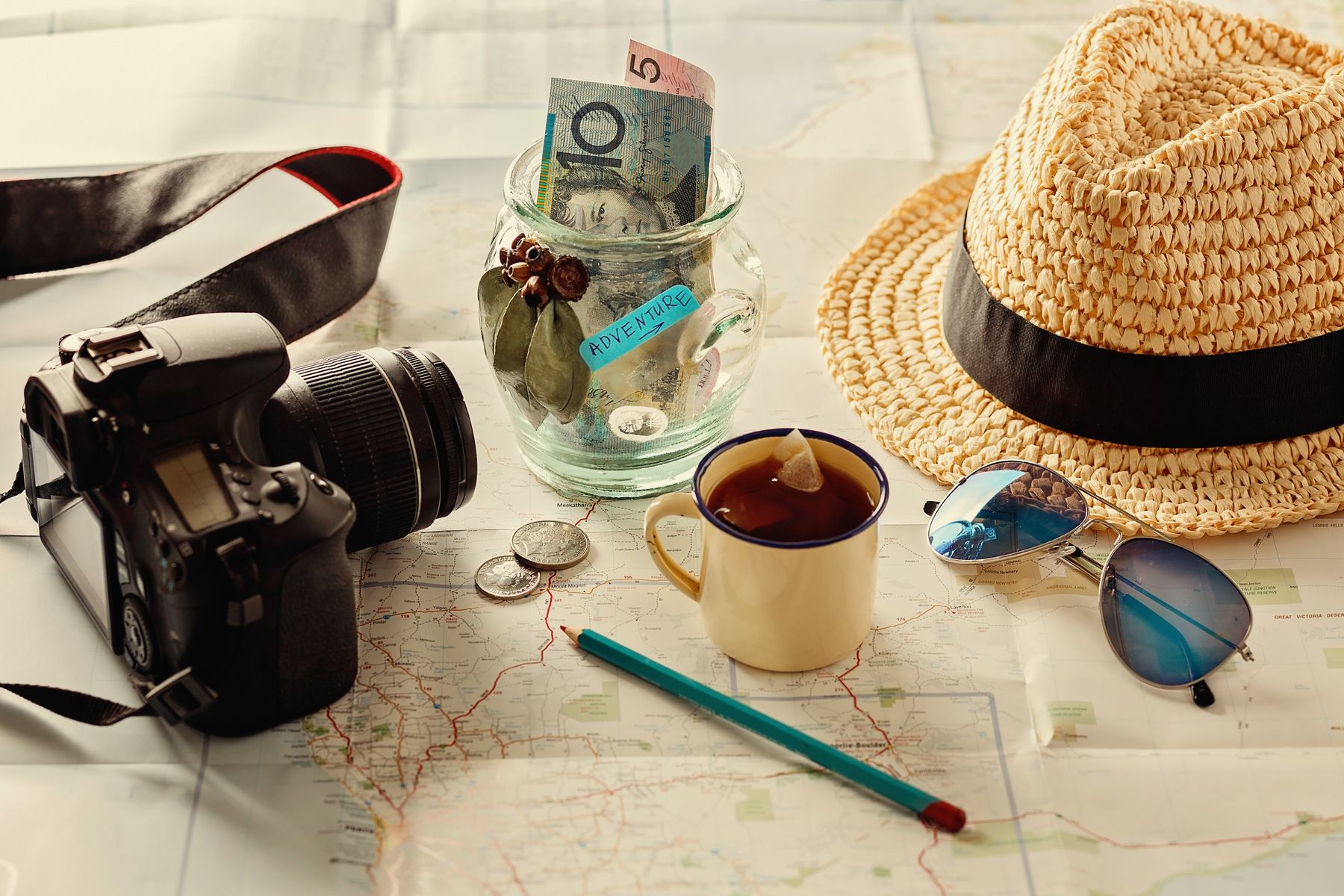 Assorted travel planning essentials such as sunglasses, money and a camera