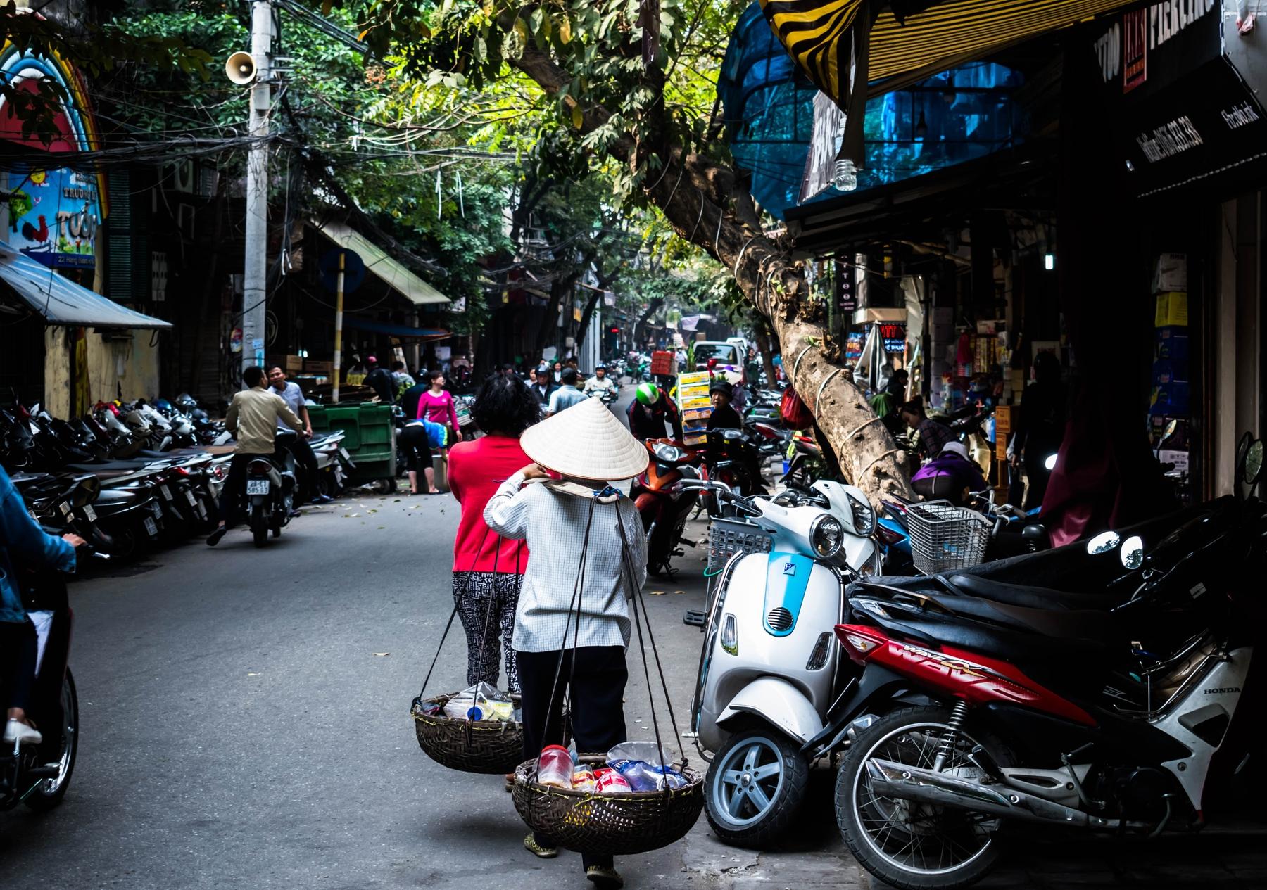 Spannende Reisefakten: Beinahe jeder Bewohner Vietnams hat ein Motorrad. Das Bild zeigt parkende Motorräder entlang einer Straße in Hanoi.