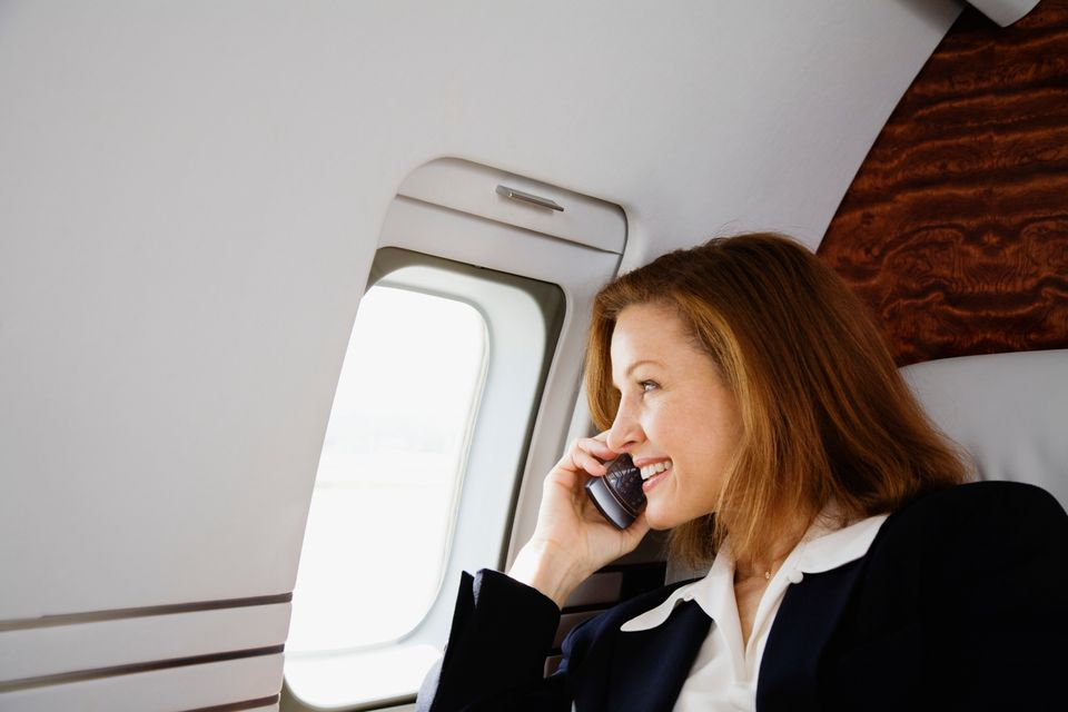 Woman speaking on the phone during a flight - 10 things you should never do when flying