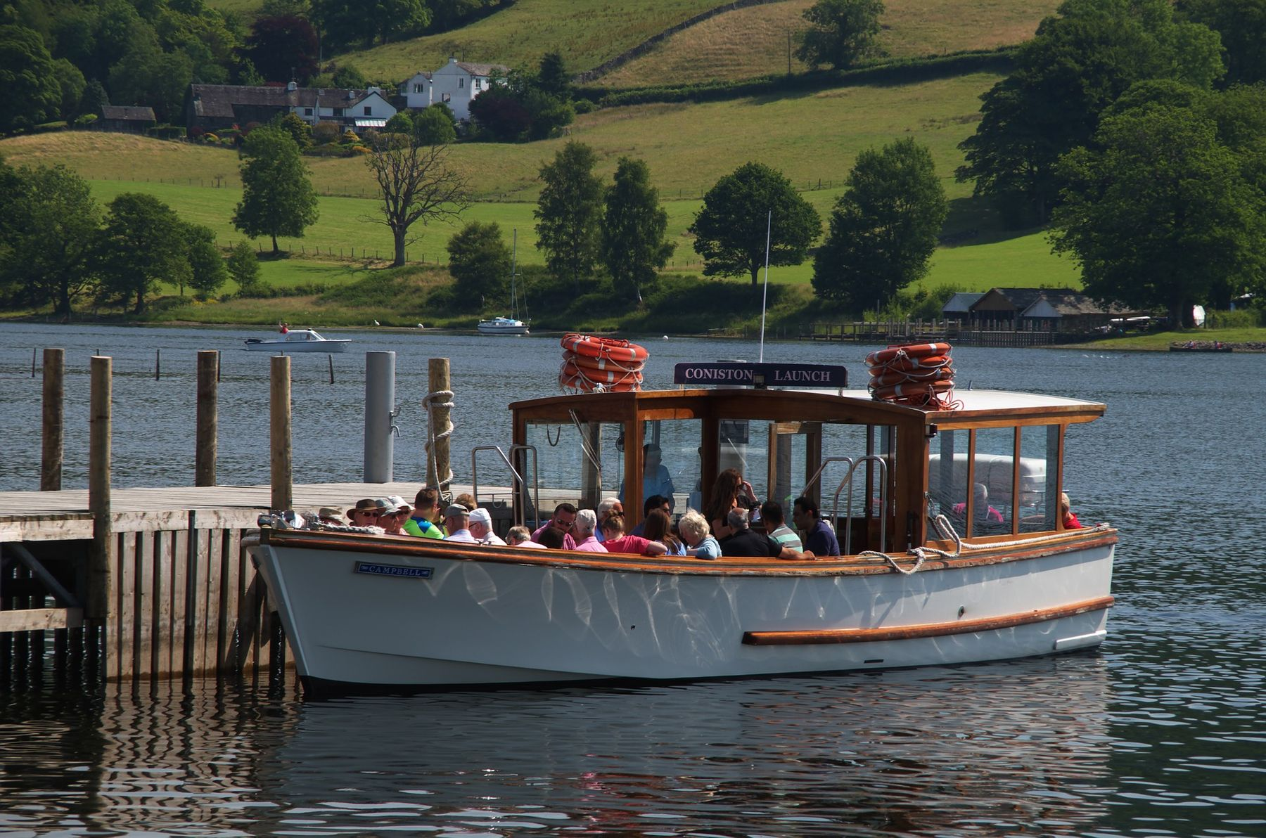 Tourists sitting on the Coniston Launch boat at the dock, about to take a trip on Coniston Water.