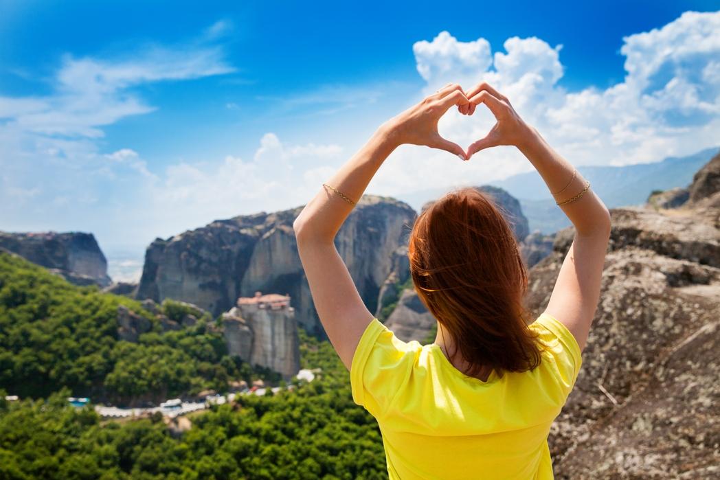 Κοπέλα με κίτρινο μπλουζάκι κάνει με τα χέρια της σχήμα καρδιάς με θέα τα Μετέωρα - Πάσχα στην Ελλάδα 2020