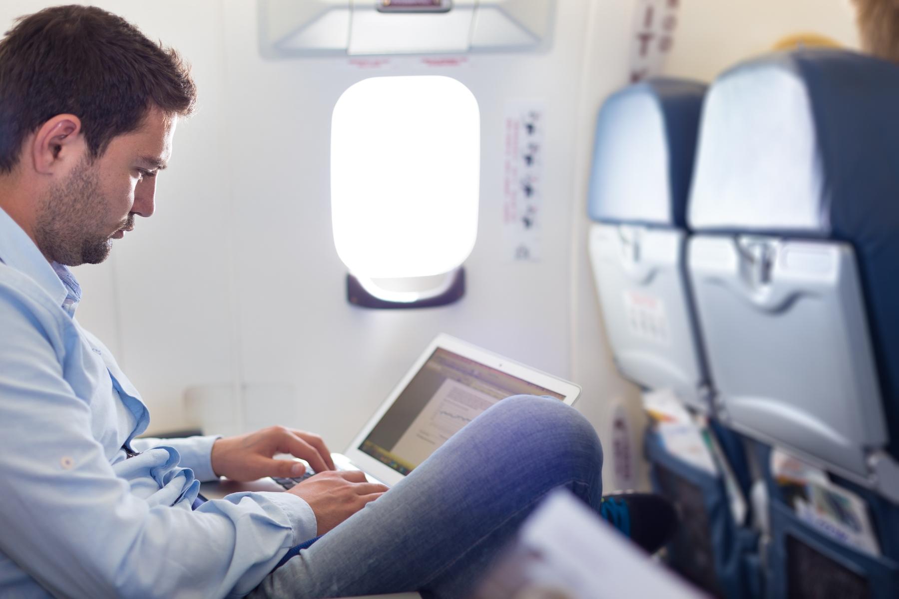 Passageiro sentado confortavelmente em sua poltrona no avião. A ITA Linhas Aéreas também tem maior espaço entre os assentos.