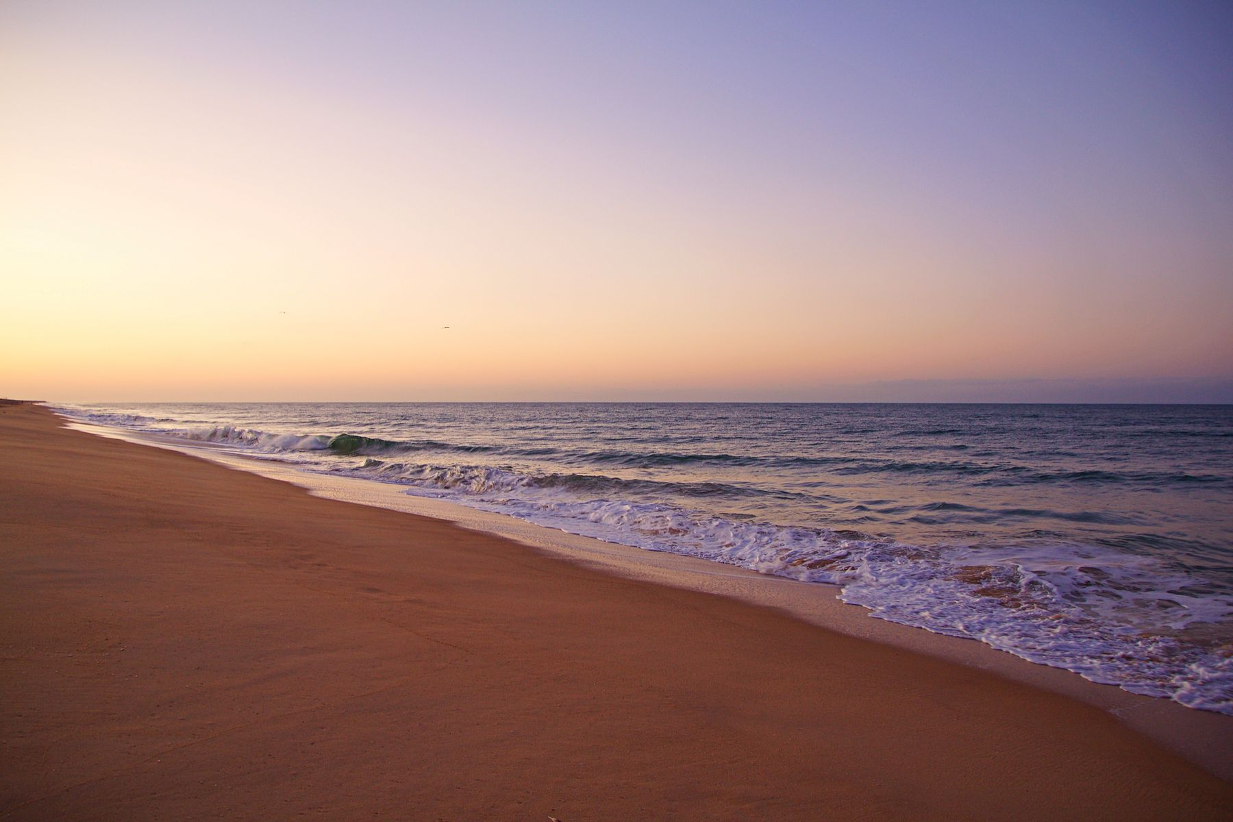 Beach waves in the Algarve, Portugal at sunset.