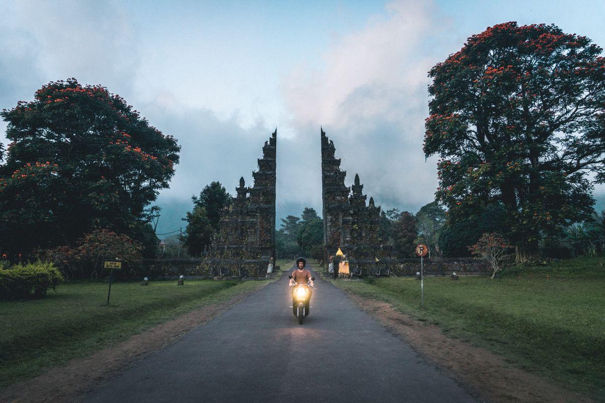 Man driving a motorbike in Bali - travel insurance, is it worth it?