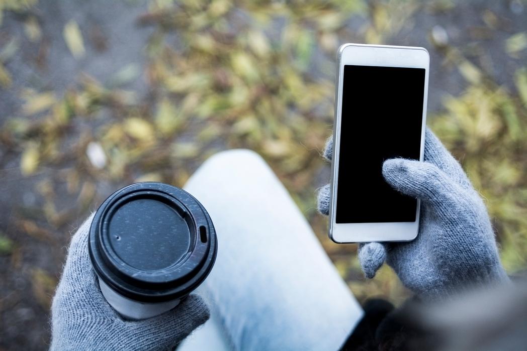 Γυναίκα κρατά το κινητό της και έναν καφέ.