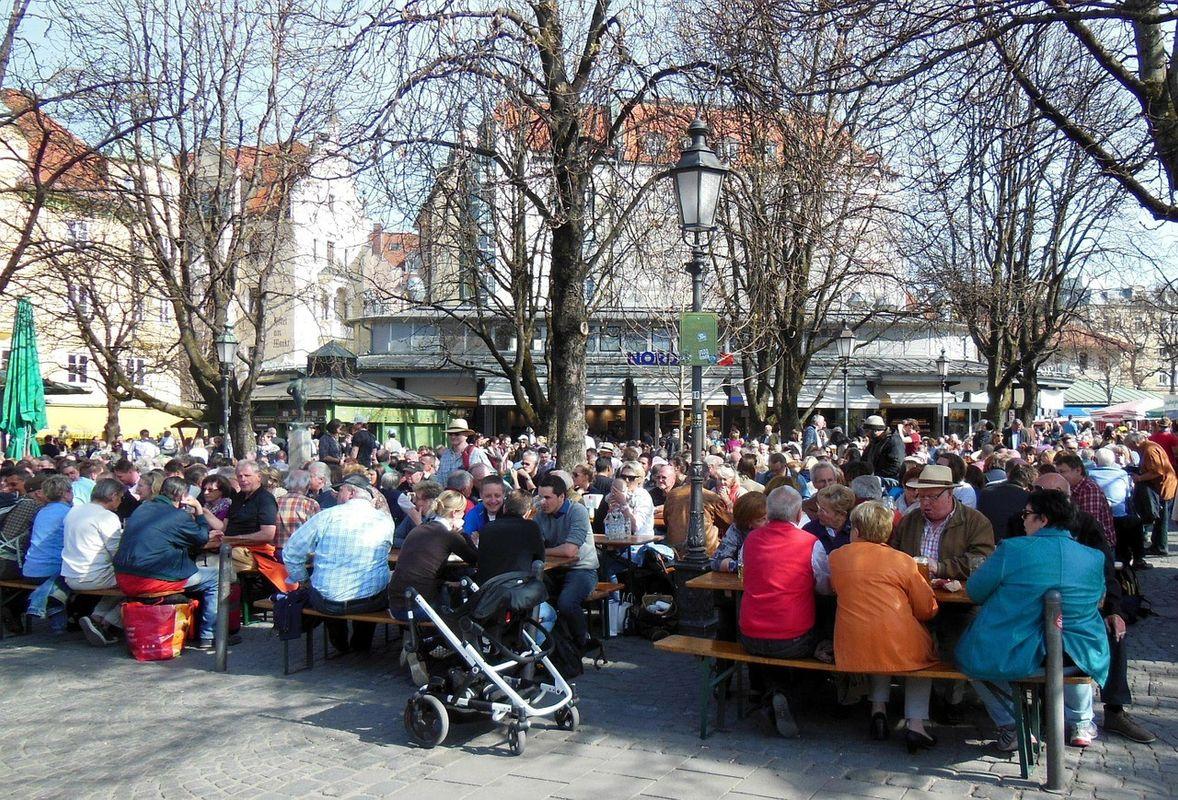 Κόσμος καθισμένος στους ξύλινους πάγκους της Viktualienmarkt - ταξίδι στο Μόναχο