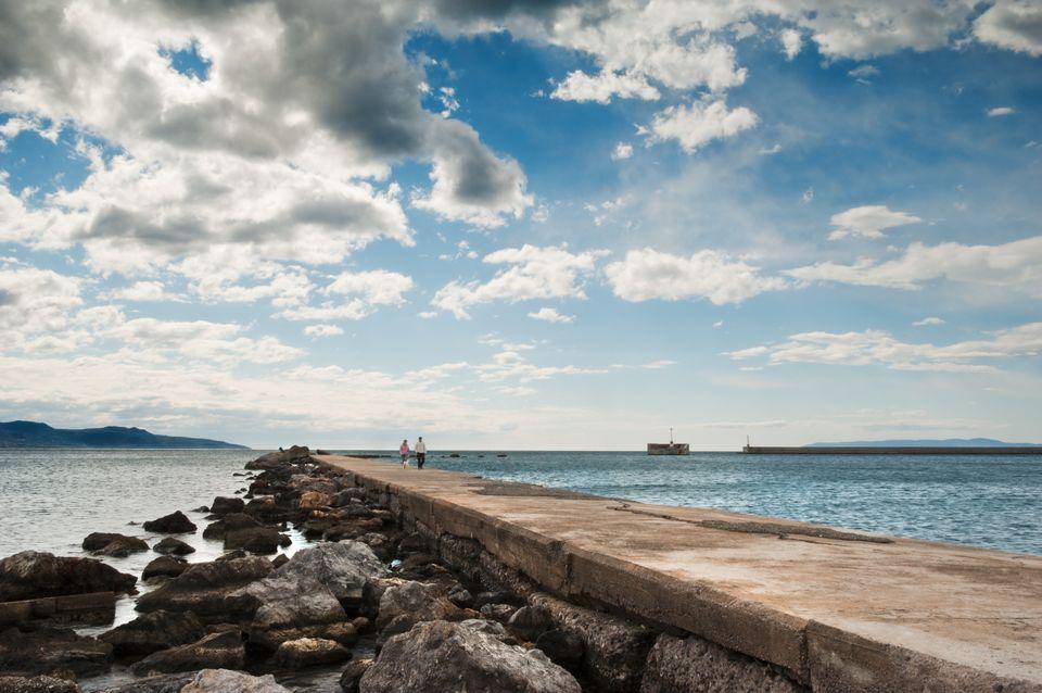 Ζευγάρι κάνει βόλτα στο Χιλιόμετρο Καλαμάτας περιτριγυρισμένο από τη θάλασσα