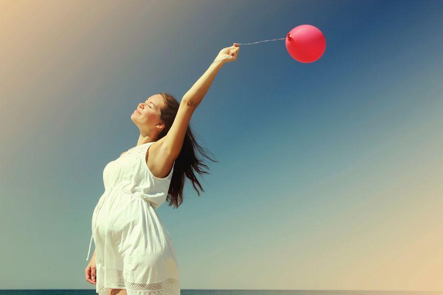 Χαρούμενη έγκυος κρατά μπαλόνι