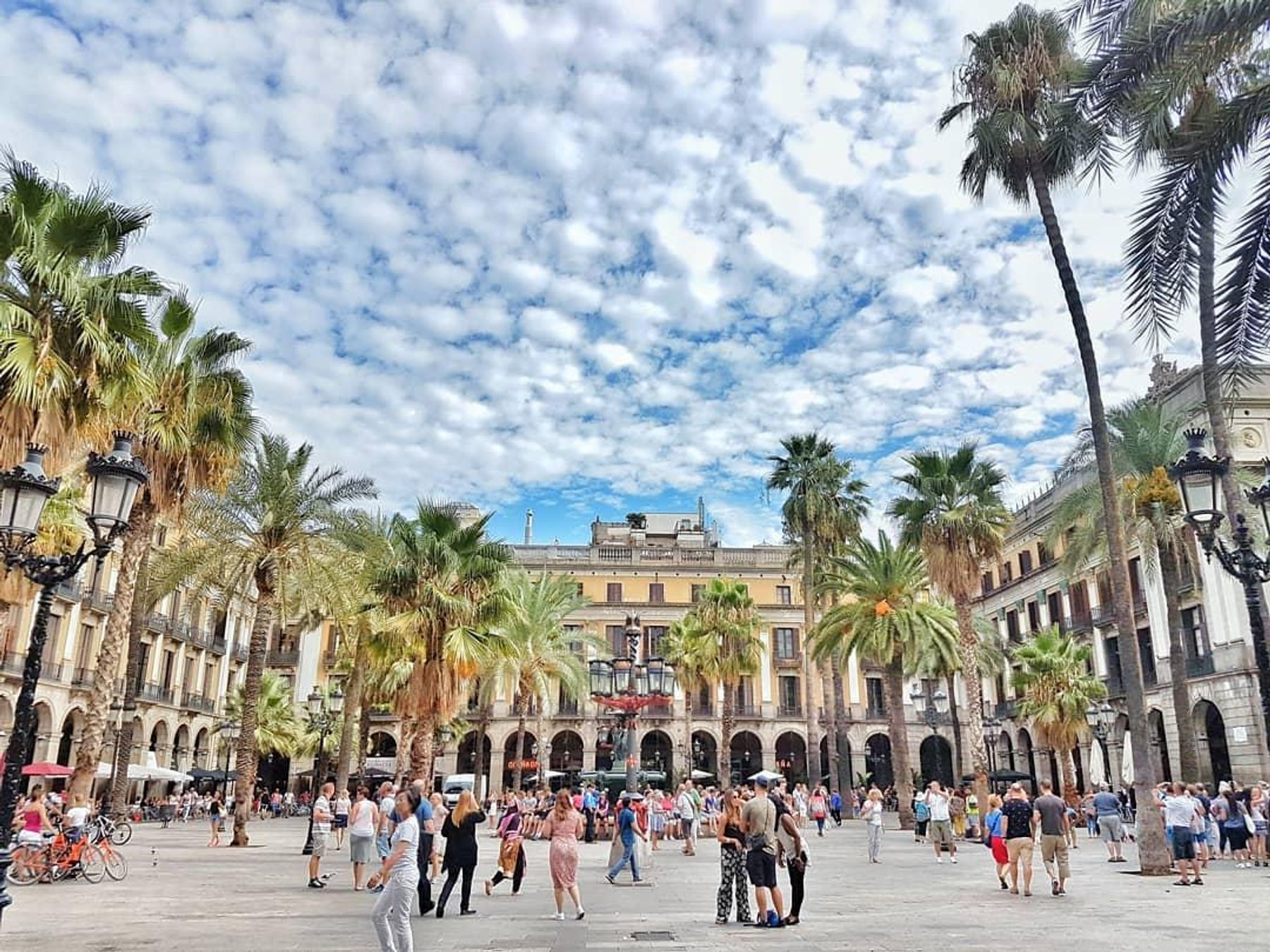A square full people. Walking tours are one of the best free things to do in Barcelona