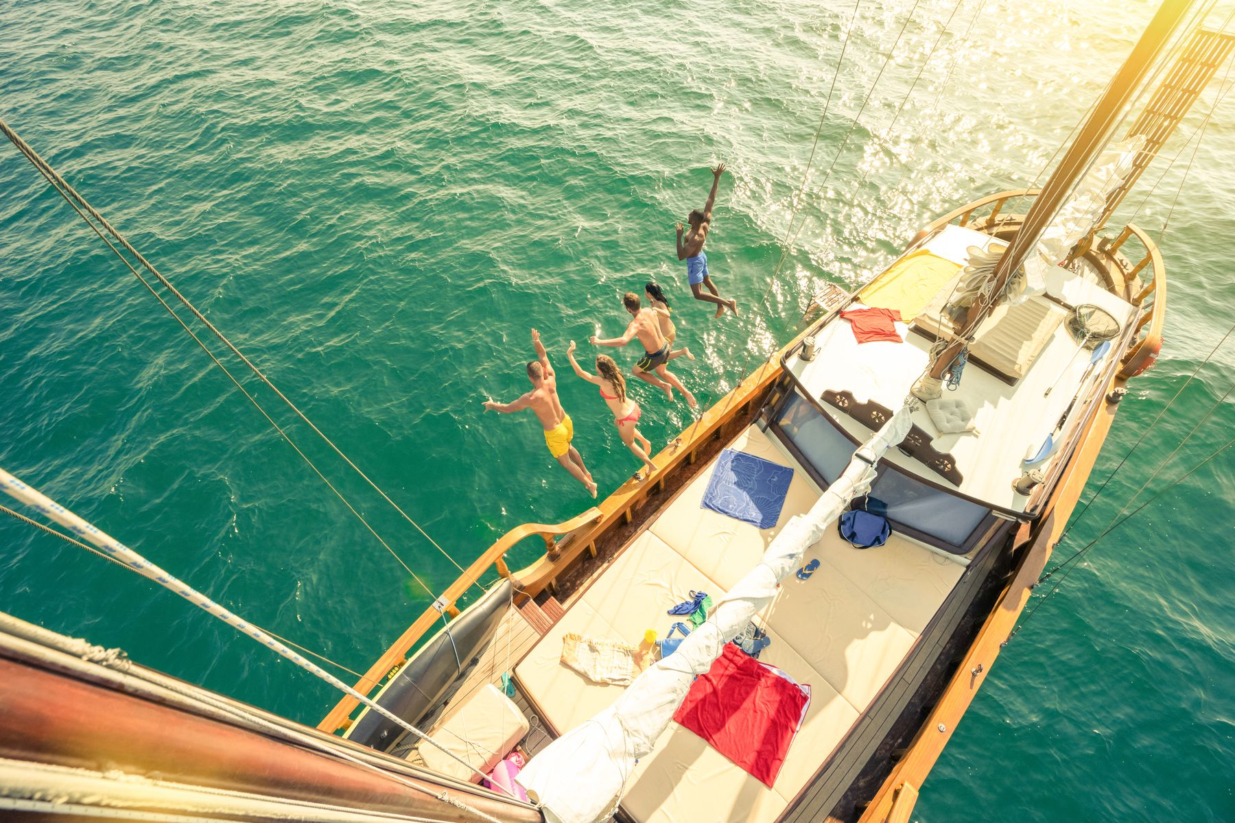 A group jumping into the water from a sailboat