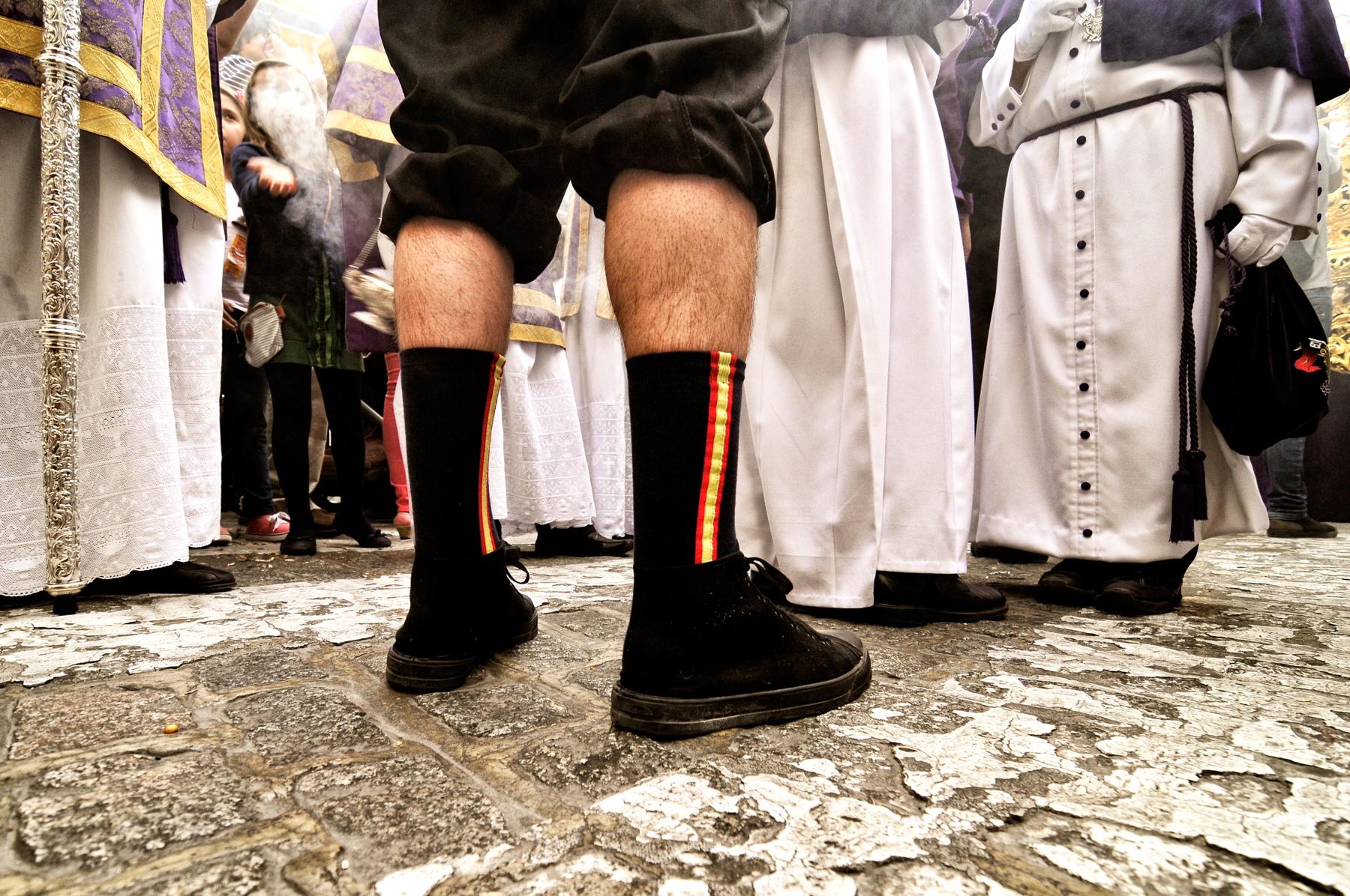 Un costalero conversa con varios penitentes y monaguillos durante una procesión © Bisual Studio