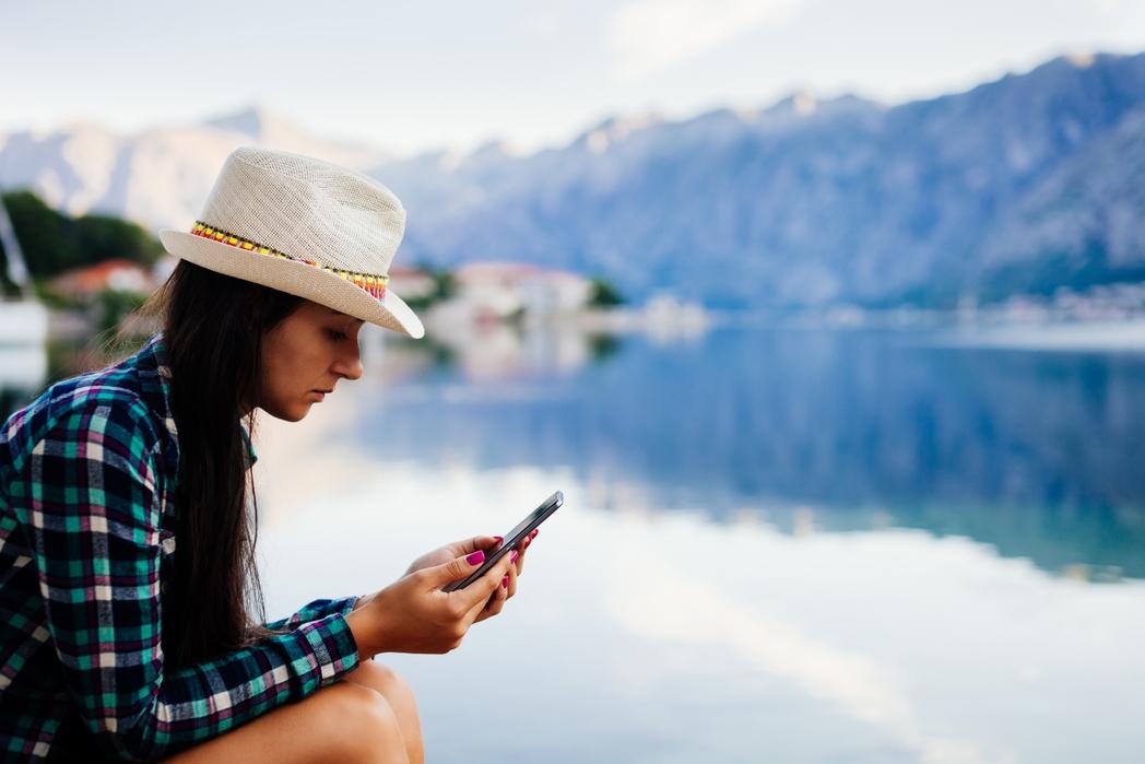 Κοπέλα κοιτάζει το κινητό της σε μια εκδρομή στο Μαυροβούνιο