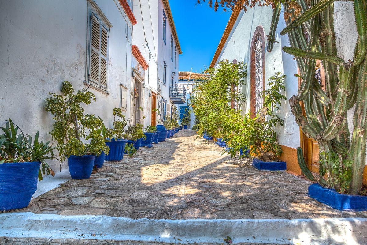 Πλακόστρωτο στενό στην Ύδρα. Γραφικά σπίτια και μπλε γλάστρες με φυτά δεξιά-αριστερά