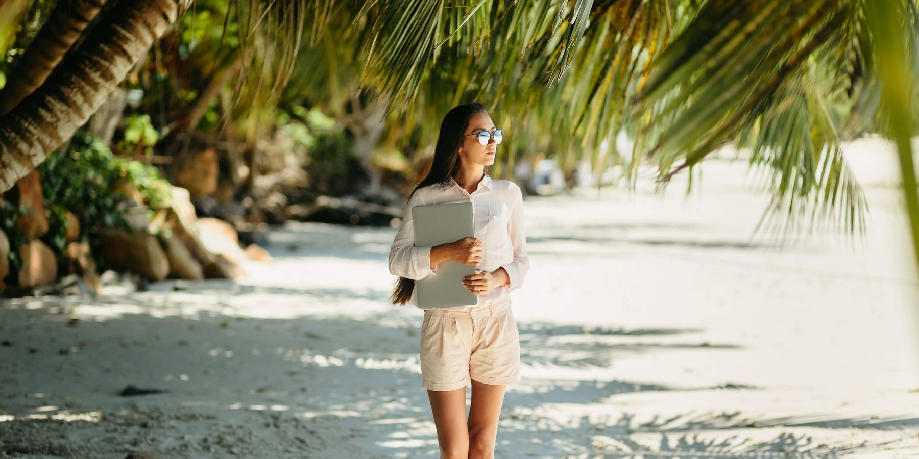 Person holding a laptop on a tropical beach with palm trees