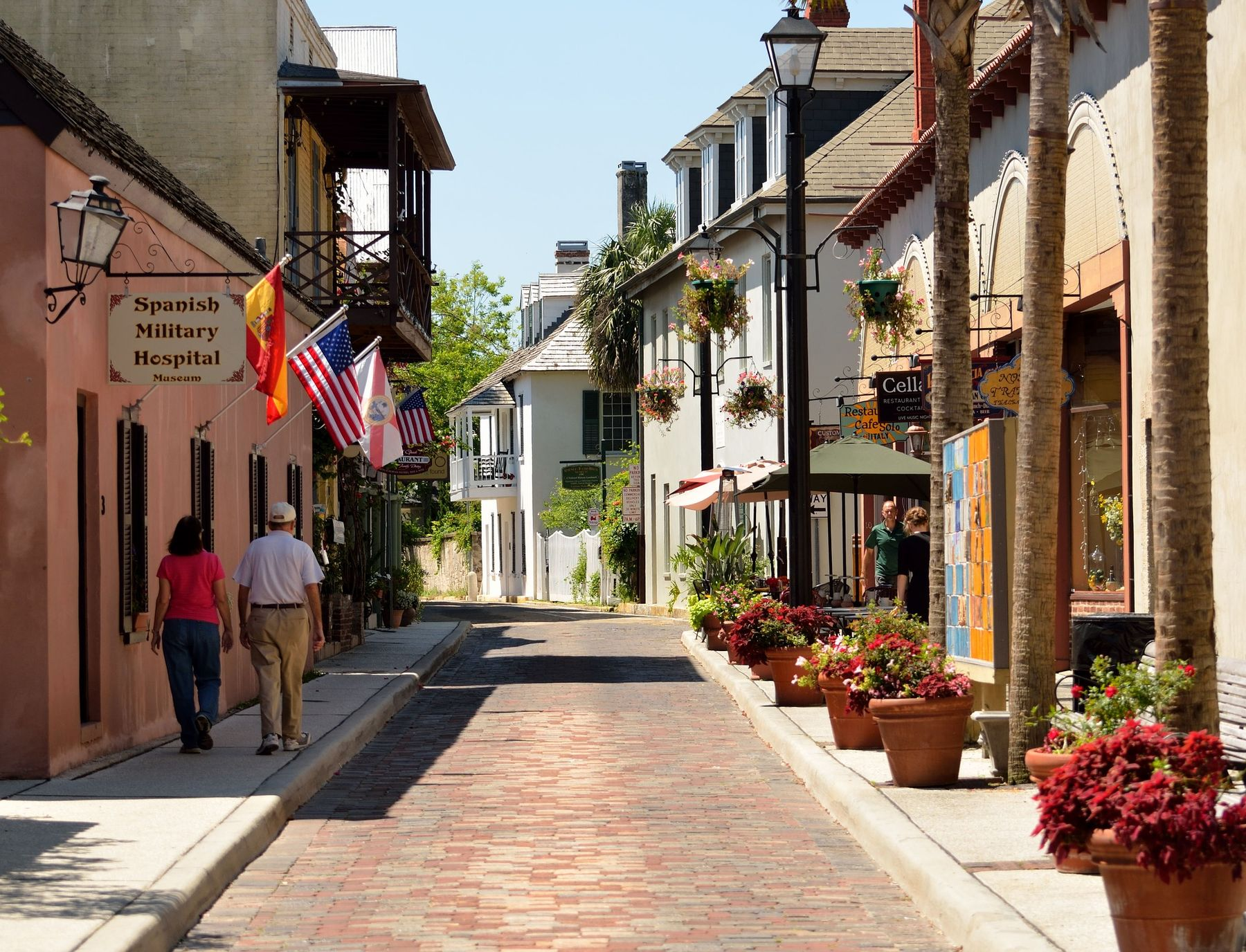 two people walking by the storefronts in st augustine florida on aviles street