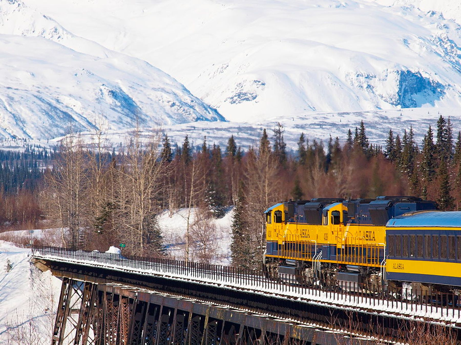 train going through snow covered mountains