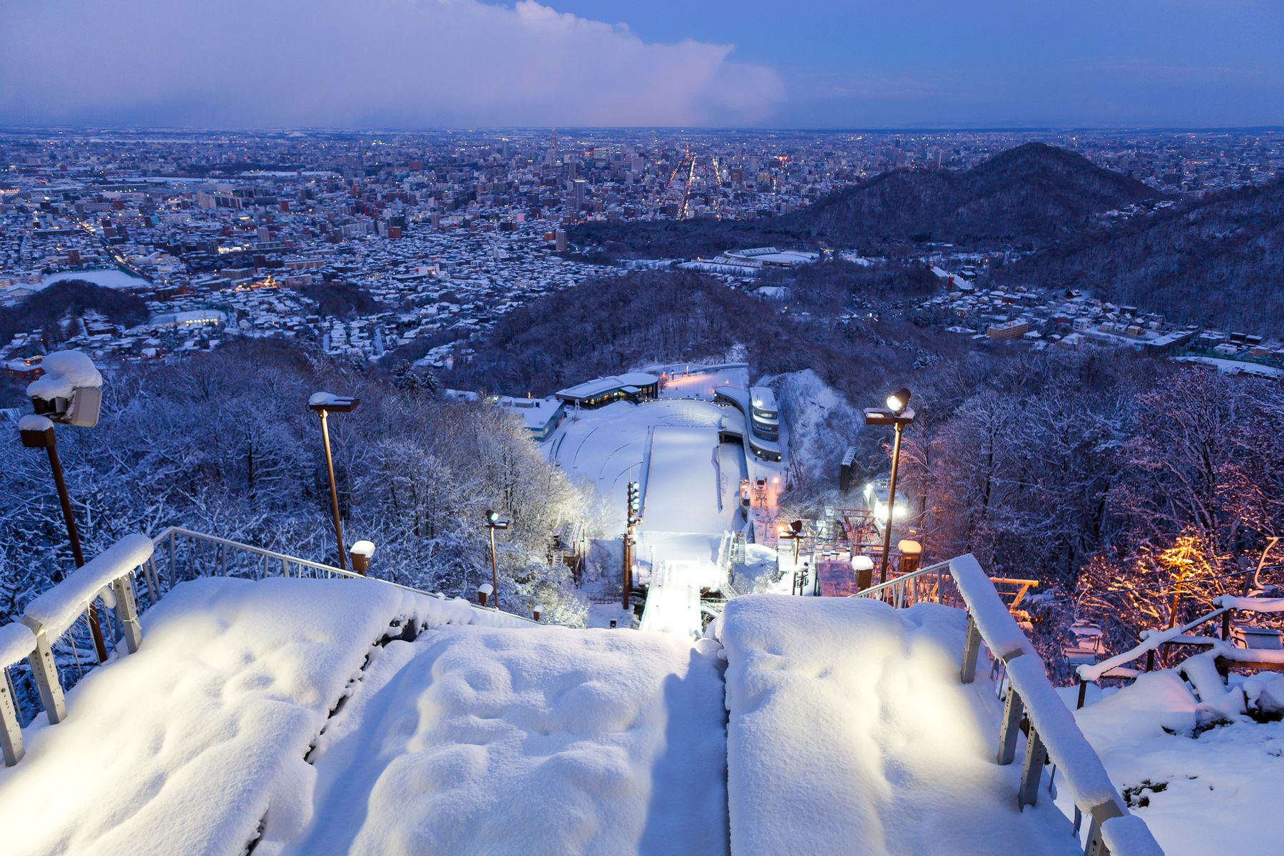 Looking down from the top of a ski jump to the lights of Sapporo city in Hokkaido, Japan.