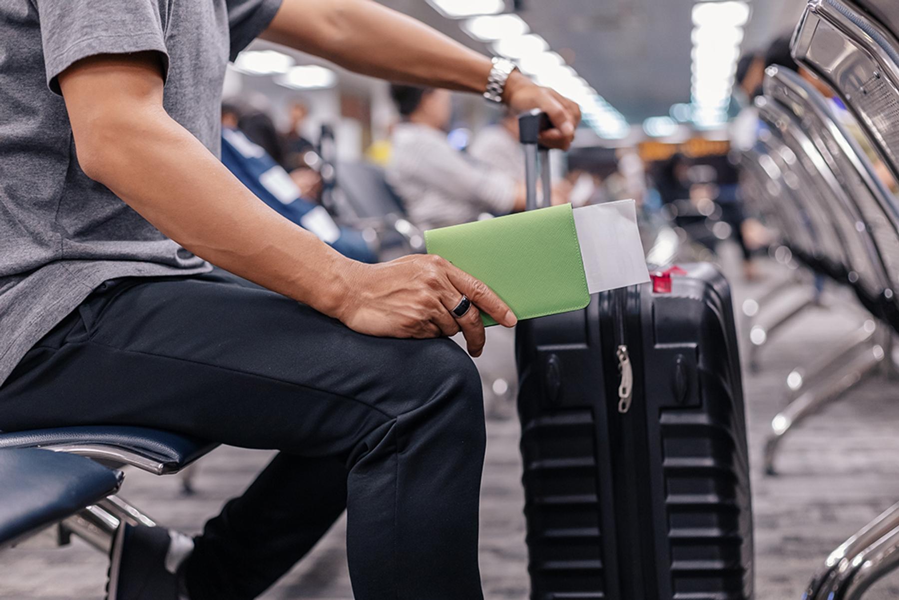 Мужчина с паспортом и чемоданом ручной клади ждет вылета в аэропорту