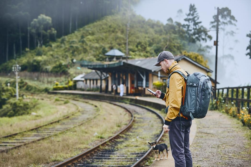 Ταξιδιώτης κοιτάζει το κινητό του περιμένοντας το τρένο στον σταθμό - συμβουλές για πράσινα ταξίδια