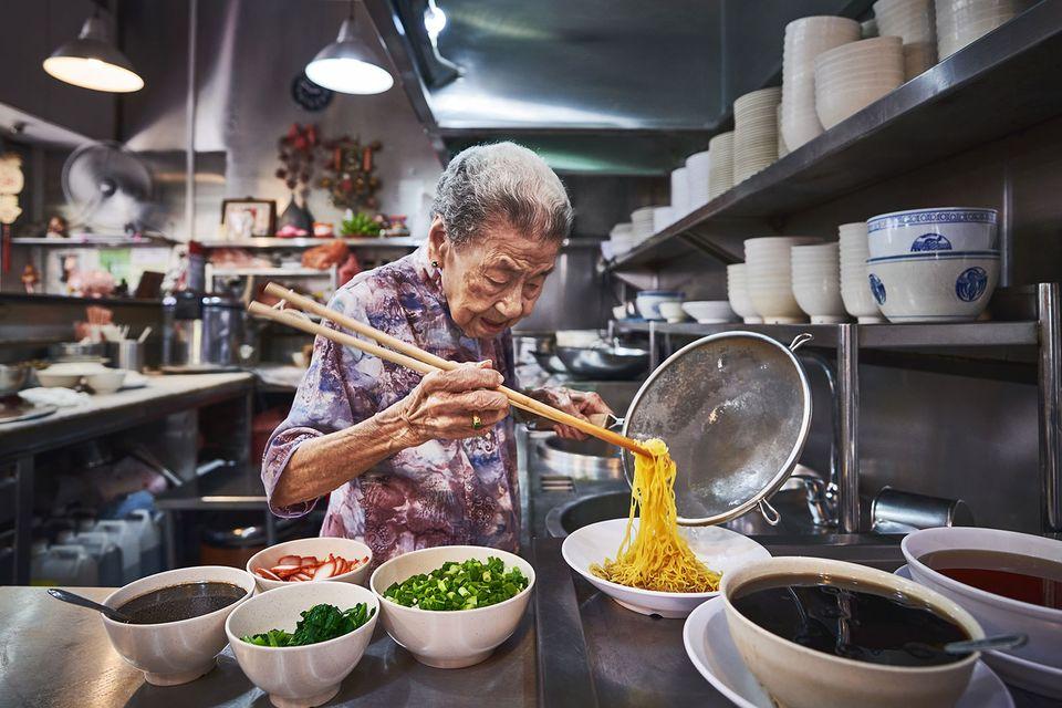 Γυναίκα σερβίρει νουντλς σε κουζίνα εστιατορίου