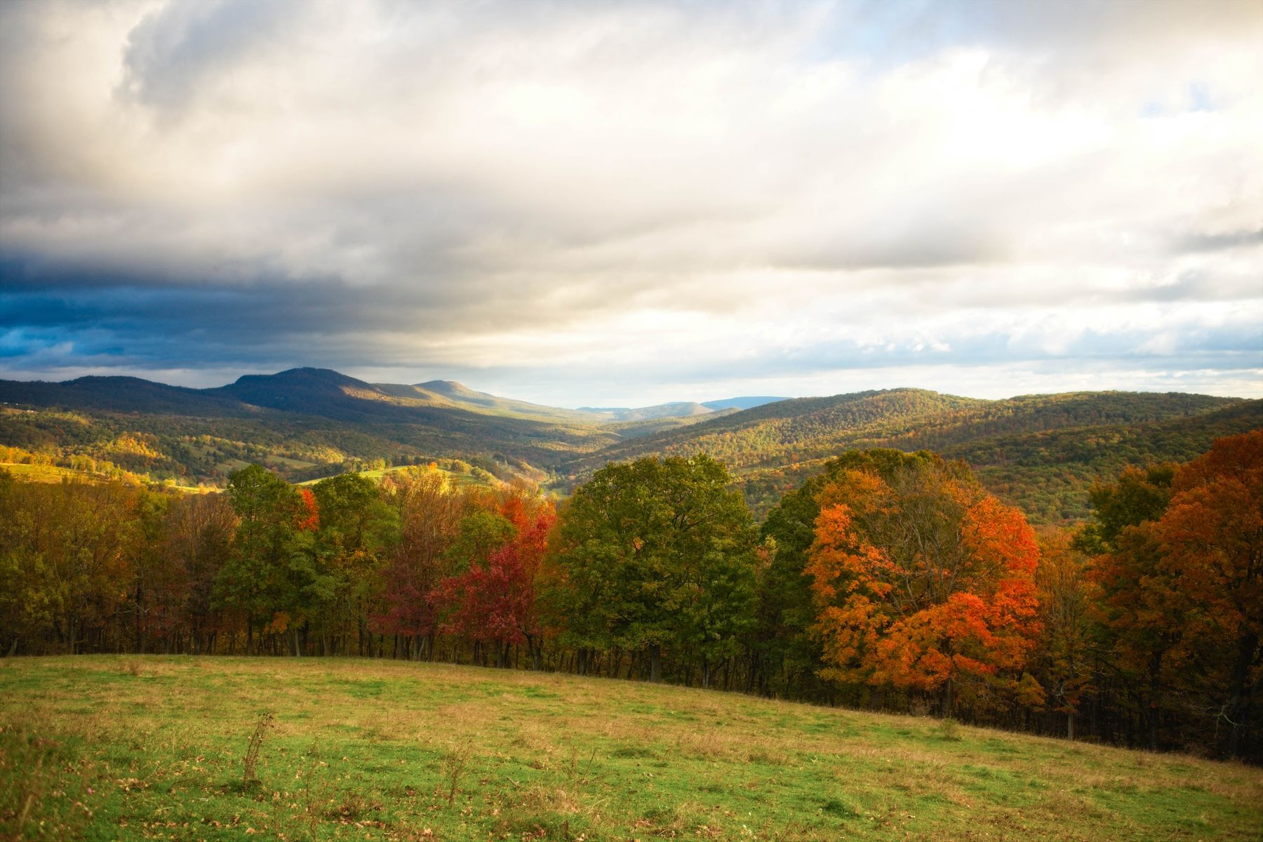 Rolling mountains covered in colorful foliage in small town America